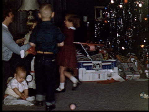 1955 ms pan children opening presents under christmas tree/ man sitting on couch with camera/ tinsel and lights on tree - prelinger archive stock-videos und b-roll-filmmaterial