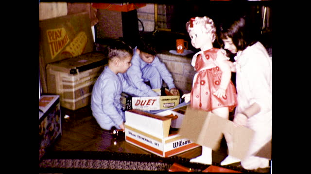children opening their presents in the living room and playing with them; girl holding up a huge doll; boy with toy trumpet in front of the fireplace - pyjamas stock videos & royalty-free footage