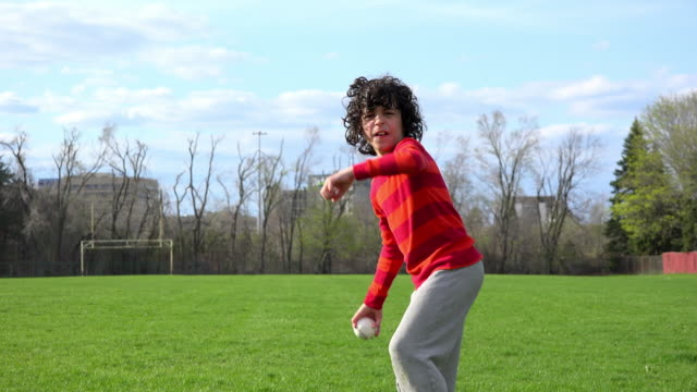Children outdoors activities: boy learns how to throw a baseball