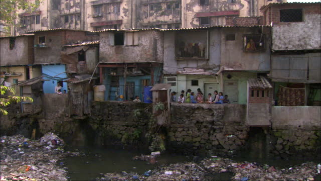 Children outside makeshift homes on riverbank. Available in HD.