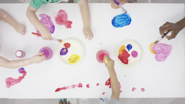 children painting on a white table surface - table top shot video stock e b–roll