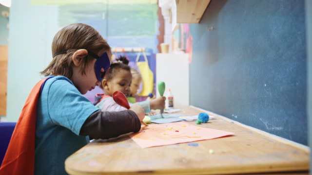 Children painting on paper at daycare