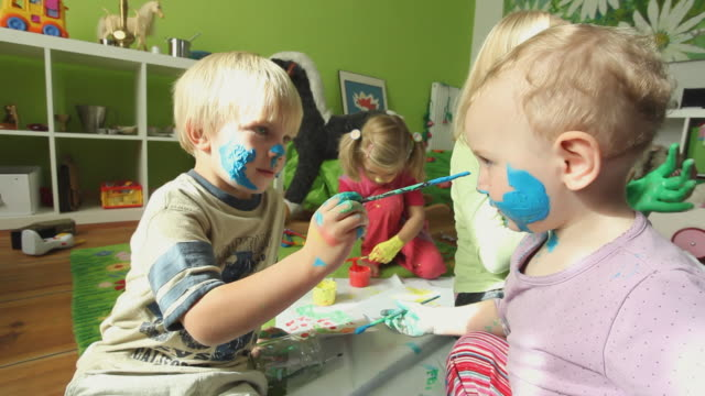 MS Children (12-23 months, 2-7 years) painting on themselves / Potsdam, Brandenburg, Germany