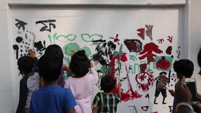 vídeos de stock, filmes e b-roll de children paints on the wall as part of the decoration for the international mother language day celebration in front of the language martyrs monument... - bagdá