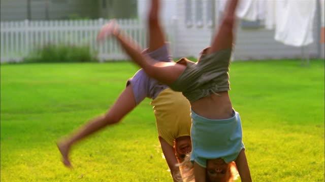 children perform cartwheels in their yard. - cartwheel stock videos & royalty-free footage