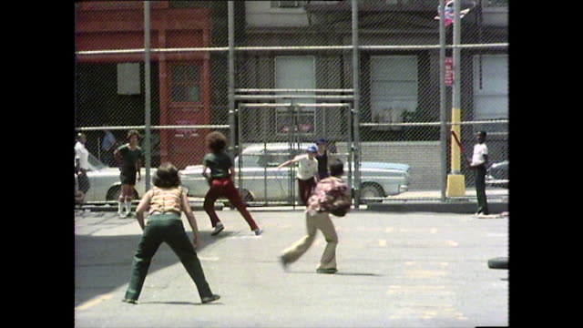 vídeos de stock e filmes b-roll de children play a make-shift ball game in manhattan, 1976 - 1976