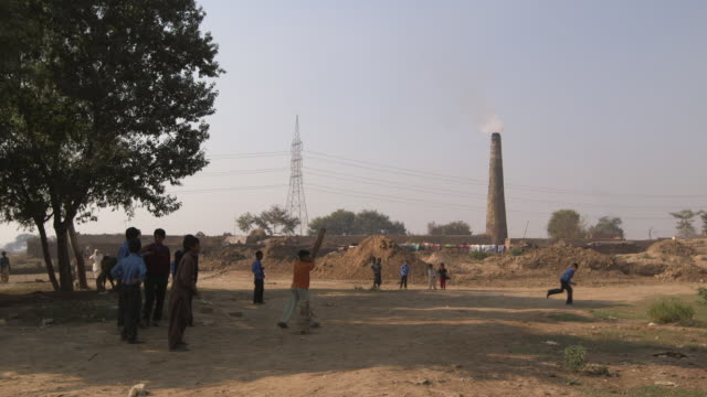 children play cricket in front of a brick kiln ,semi rural setting,punjab - punjab pakistan stock videos & royalty-free footage