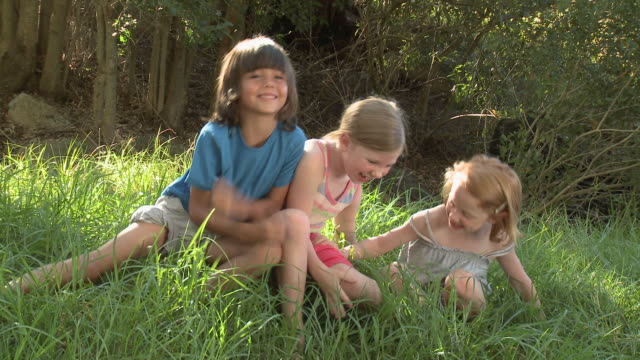 Children play fighting in grass
