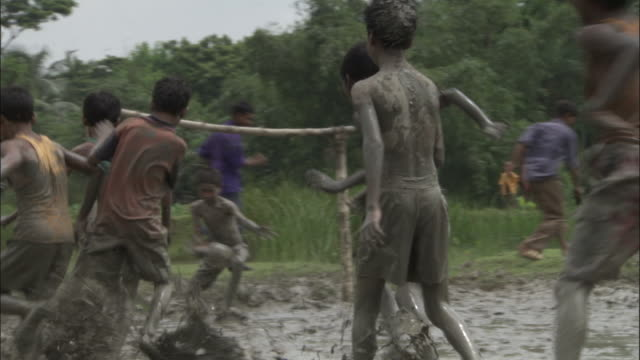 children play football in mud available in hd. - schlamm stock-videos und b-roll-filmmaterial