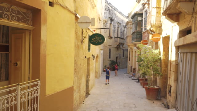 children play football/soccer in old town - malta - gasse stock-videos und b-roll-filmmaterial