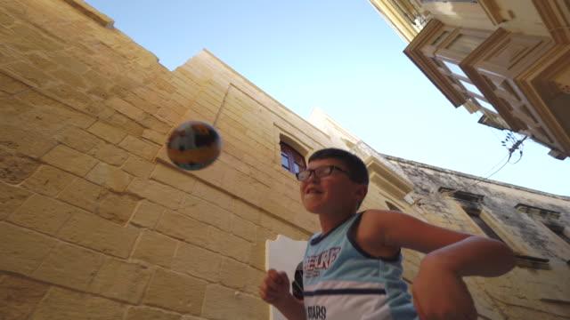 children play football/soccer in old town - malta - geköpft stock-videos und b-roll-filmmaterial