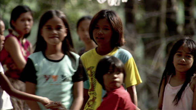 Children play games in a jungle village.
