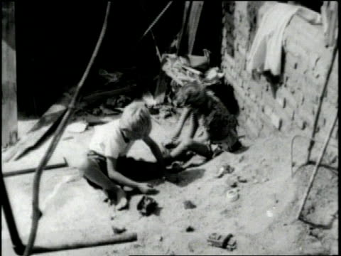 stockvideo's en b-roll-footage met children play in dirt near debris in the aftermath of world war ii. - 1946