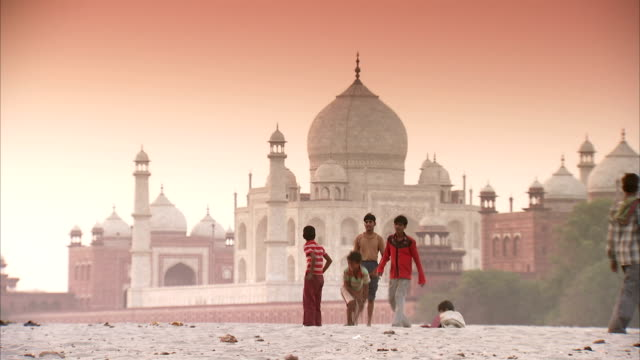 vídeos de stock e filmes b-roll de children play in front of the taj mahal at sunrise. - taj mahal