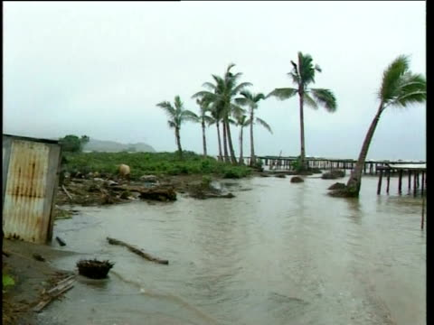 Children play in polluted waters of tropical beach damaged by rising sea levels Fiji