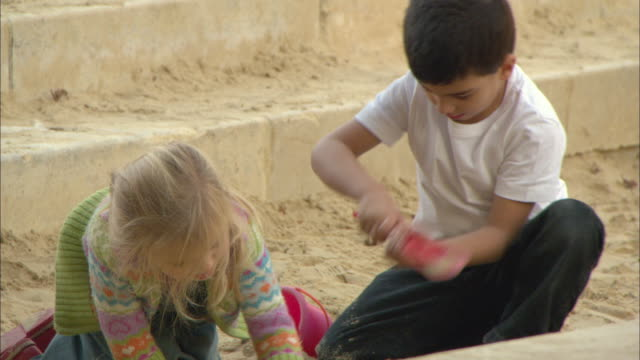 vidéos et rushes de ms pan children play in sandbox at playground / paris, france - 2 kid in a sandbox