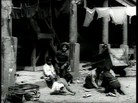 stockvideo's en b-roll-footage met 1939 ws children play in the dirt in low-income neighborhood / charleston, south carolina - racisme