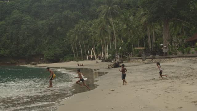 children play on beach at sunset - bali - jungen stock-videos und b-roll-filmmaterial