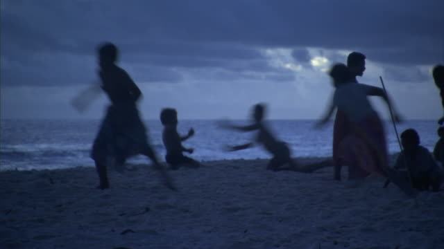 children play on beach at sunset, solomon islands - pacific islands stock videos & royalty-free footage