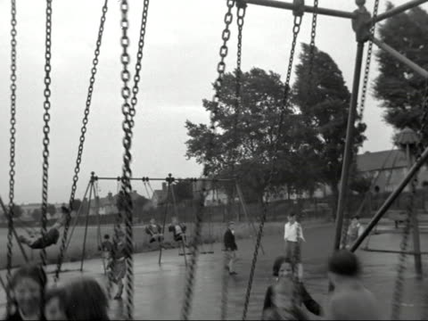 children play on swings and roundabouts in a park - playground stock videos & royalty-free footage