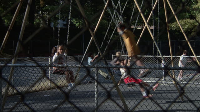 Children play on swings in a playground.