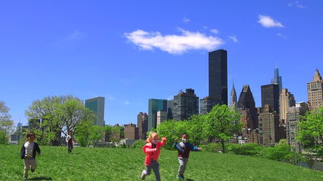 children play on the hill in springtime at roosevelt island amidst the pandemic of covid-19 in new york city, new york on may 6, 2021. - baby girls stock videos & royalty-free footage