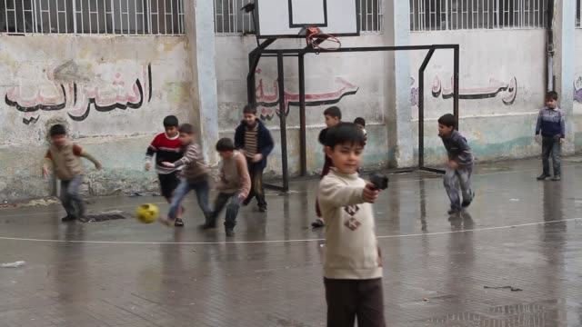 children play on the school grounds of a newly opened school in aleppo syria - toy gun stock videos & royalty-free footage