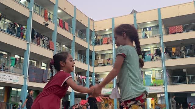 children play outside a unrwa school, where some families are now living, following israeli raids on may 19, 2021 in gaza city, gaza. - striscia di gaza video stock e b–roll
