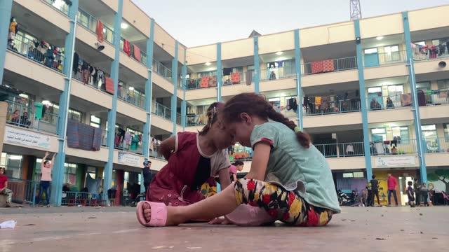 children play outside a unrwa school, where some families are now living, following israeli raids on may 19, 2021 in gaza city, gaza. - ガザ地区点の映像素材/bロール