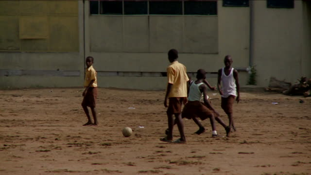 Children play soccer on a dirt pitch. Available in HD.