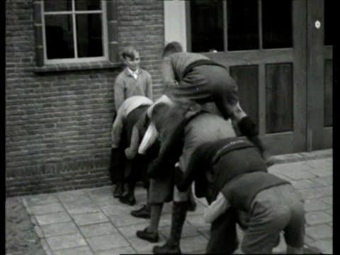 stockvideo's en b-roll-footage met children play 'soldiers' and other children's games on street / haarlem noordholland netherlands - noord holland