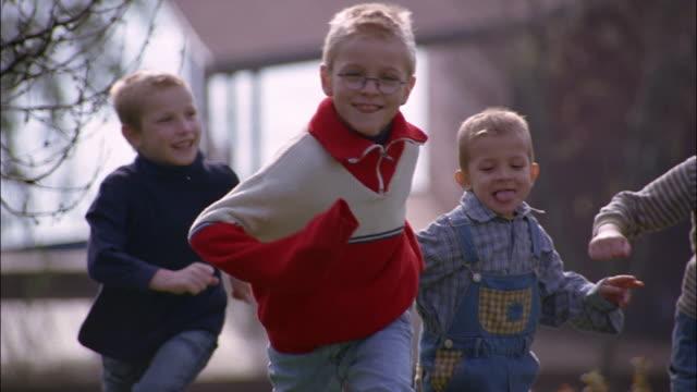 children play tag in a backyard. - romania stock-videos und b-roll-filmmaterial