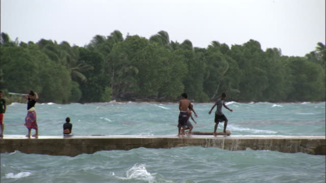 children play with football on jetty at high tide, funafuti atoll, tuvalu - pacific islands stock videos & royalty-free footage