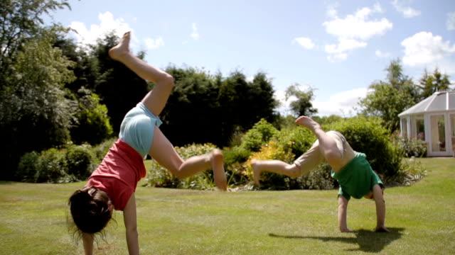 children playing acrobats in the garden - cartwheel stock videos & royalty-free footage