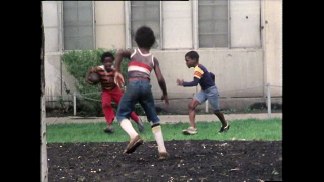 vídeos de stock e filmes b-roll de children playing american football on grass; 1979 - afro americano