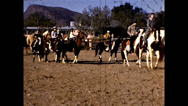 stockvideo's en b-roll-footage met children playing around the cactus garden with dog and climbing to the top of a rusted wagon; people on horseback inside a ranch, golden retriever... - dog run
