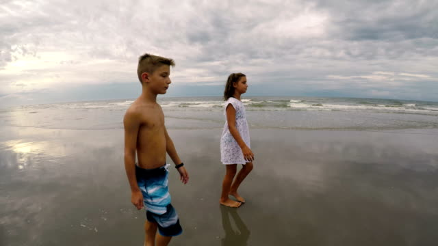 children playing at beach on overcast day - shirtless stock videos and b-roll footage