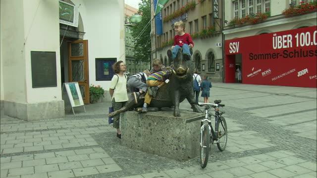 WS PAN Children playing at boar statue and pedestrians in Marienplatz, Munich, Bavaria, Germany