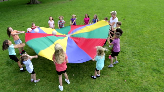 children playing ball games with a parachute - parachute stock videos & royalty-free footage