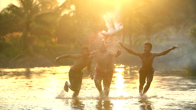 Children playing catch a duck in the river.
