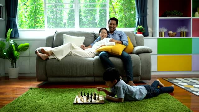 vidéos et rushes de enfants 4k jouant des échecs dans un salle de séjour tout en souriant parent le regardant sur le sofa à la maison - planche de bois