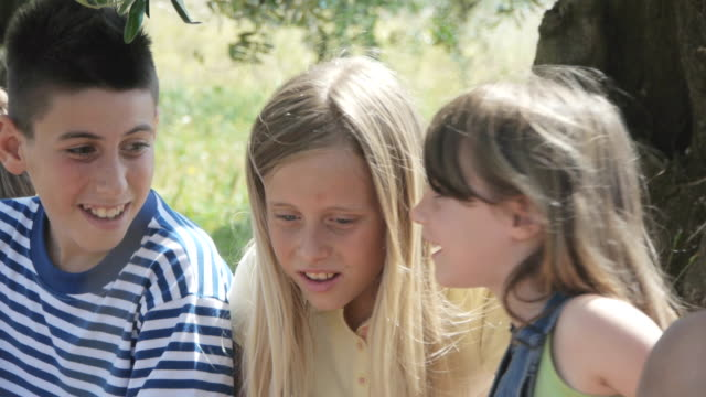 vidéos et rushes de children playing chinese whispers - toscane