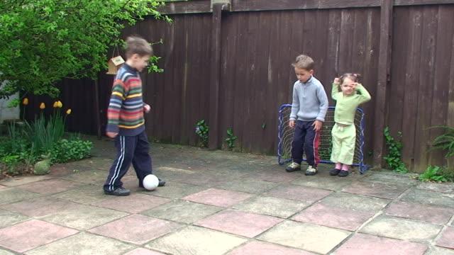 Enfants jouant au football dans le jardin