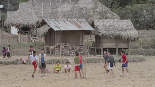 ws children playing game of kick volleyball / xam neua, laos - tetto di paglia video stock e b–roll