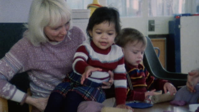 1983 montage children playing in a daycare, and a doctor coaxing a child to stack building blocks / london, england - kindergartengebäude stock-videos und b-roll-filmmaterial