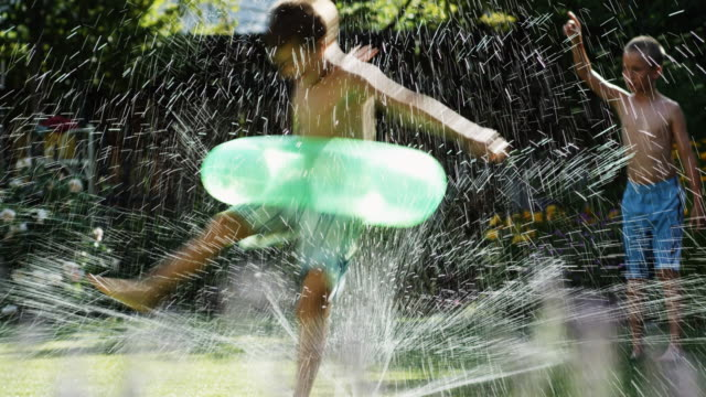 children playing in a sprinkler - see other clips from this shoot 1421 stock videos & royalty-free footage