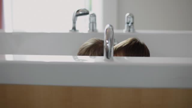 ms children (2-5) playing in bathtub / kleinmachnow, brandenburg, germany - hiding stock-videos und b-roll-filmmaterial