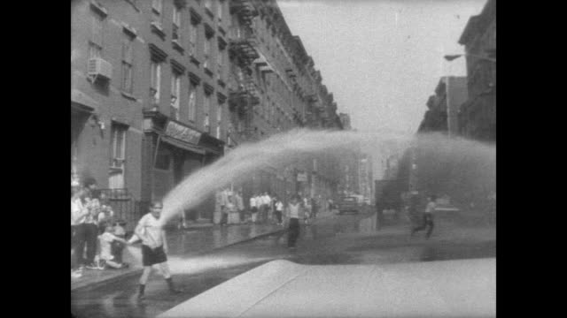 vídeos y material grabado en eventos de stock de children playing in fire hydrant on nyc streets as water is sprayed everywhere. - boca de riego