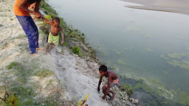 stockvideo's en b-roll-footage met children playing in front of their house at the river tista during rainy season their houses are eroded by flood and they shift to another places - vluchteling ontheemden
