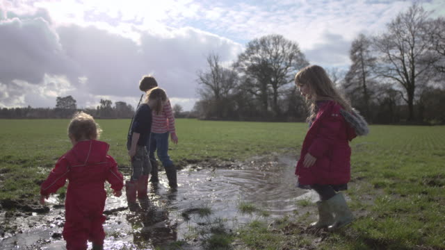 children playing in muddy puddles - mud stock videos and b-roll footage